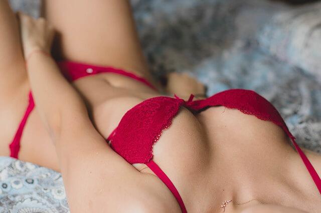femme en sous-vêtements rouges allongée sur un lit